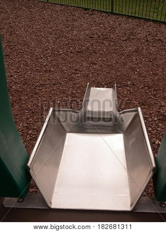 A Close Up Shot Of A Metal Slide In A Child's Playground With Bark Wooden Chips For Safety, Accident