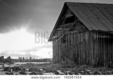 The springtime sun sets behind an old barn house in the Northern Finland. The snow has started to melt and the days are a bit warmer.