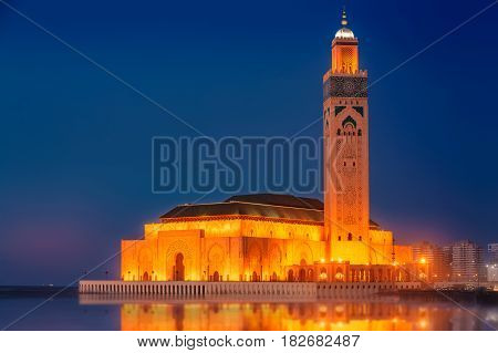 The Hassan II Mosque reflecting in the ocean. Shot after sunset at blue hour in Casablanca, Morocco.