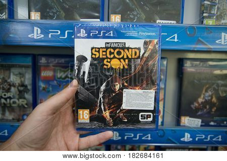 Bratislava, Slovakia, circa april 2017: Man holding Infamous Second son videogame on Sony Playstation 4 console in store