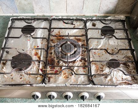 The Full Display Of A Dirty Gas Metal Top Hob With Several Plates And Dials Turned Off, In An Unclea