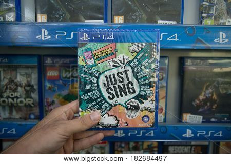 Bratislava, Slovakia, circa april 2017: Man holding Just Sing videogame on Sony Playstation 4 console in store
