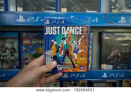Bratislava, Slovakia, circa april 2017: Man holding Just Dance 2017 videogame on Sony Playstation 4 console in store