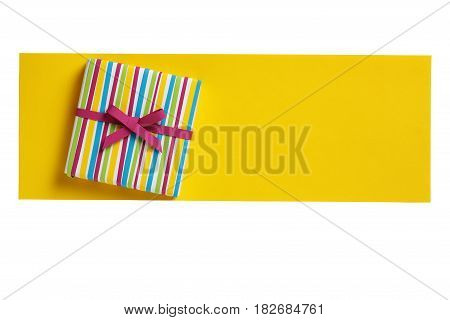 Сolorful gift box on the yellow paper letter blank isolated on white background