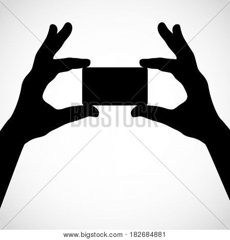 Two hands hold a card with their fingers. Silhouettes. Element for your design.
