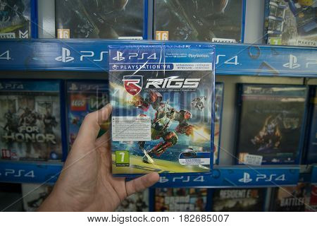 Bratislava, Slovakia, circa april 2017: Man holding Rigs Mechanized Combat League VR videogame on Sony Playstation 4 console in store