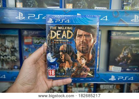 Bratislava, Slovakia, circa april 2017: Man holding The Walking Dead The Telltale Series - A New Frontier videogame on Sony Playstation 4 console in store