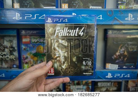 Bratislava, Slovakia, circa april 2017: Man holding Fallout 4 videogame on Sony Playstation 4 console in store