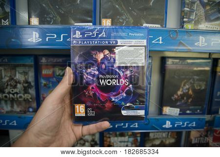 Bratislava, Slovakia, circa april 2017: Man holding Playstation Worlds VR videogame on Sony Playstation 4 console in store