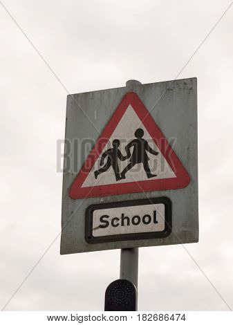 A Red White And Black School Crossing Sign With A Cloudy Sky Background