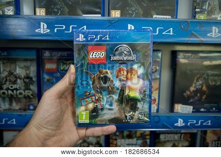 Bratislava, Slovakia, circa april 2017: Man holding Lego Jurassic World videogame on Sony Playstation 4 console in store