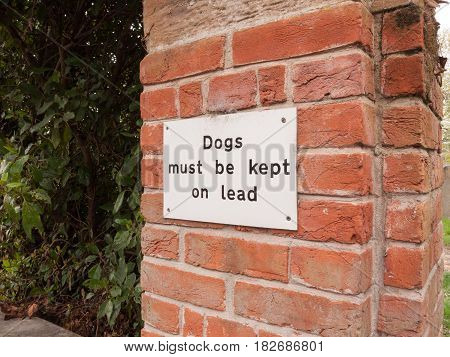 A Dogs Must Be Kept Of Lead White And Black Simple Sign Nailed To A Brick Wall On The Outside Near A