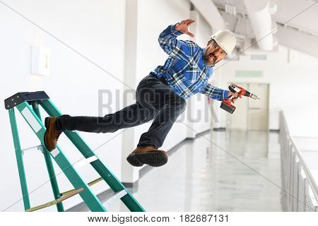Senior worker falling off ladder inside building