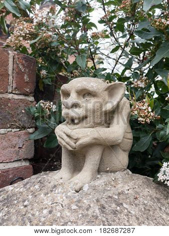 A Strange Goblin Gremlin Concrete Statue On A Pillar Outside With Fangs And Big Ears Creepy Scary