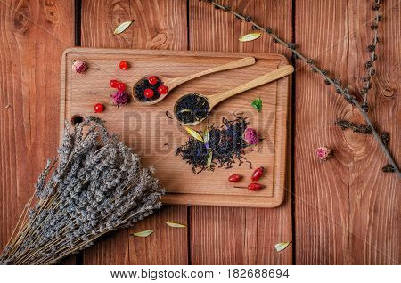 Black Tea With Herbs In Wooden Spoons  On A Wooden Board Decorated Flowers