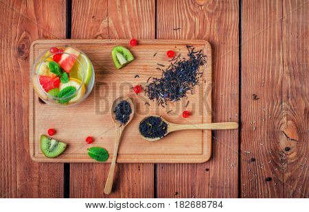 Black Tea With  In Wooden Spoons  On A Wooden Board Decorated  With Kiwi, Leaf Of Mint, Banana,
