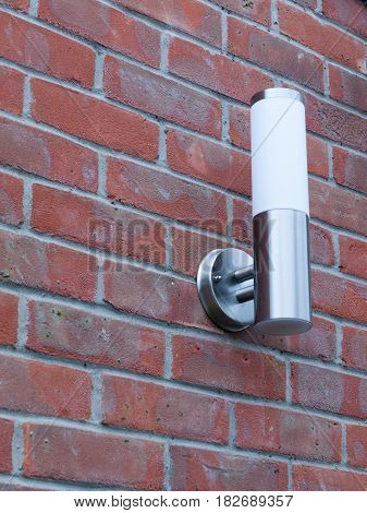 an outside metal and white modern lamp turned off not on near front door in the day light and on brick wall behind domestic cool silver