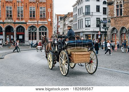 Bruges Belgium - July 29 2016: Horse carriage for tourists in Markt Square in the city of Bruges. The historic city centre is a World Heritage Site of UNESCO. It is known for his picturesque cobbled lanes and dreamy canals