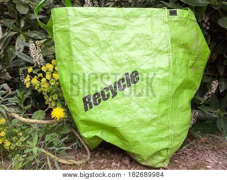an eco friendly recycle green long life bag outside on the ground near bushes environment clean posh conscious caring environmental modern