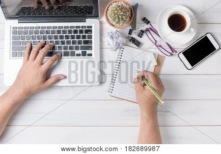 business hand man using computer and writing on blank notebook Modern white office desk table with laptop and other supplies with cup of coffee. Top view flat lay.