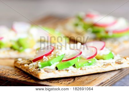 Diet and quick veggie cracker with sauce and vegetables. Fresh avocado and radishes on crispy cracker with seeds on wooden board. Closeup
