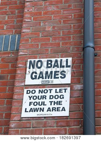 A Sign Outside Up On The Wall White And Black Saying No Balls Games Do Not Let Your Dog Foul The Law