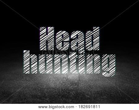 Finance concept: Glowing text Head Hunting in grunge dark room with Dirty Floor, black background
