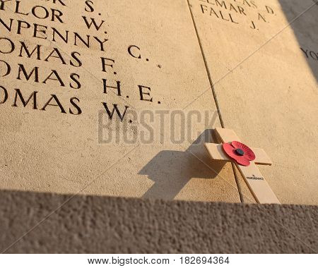 IEPER, BELGIUM, APRIL 8 2017: A poppy memorial cross left poignantly at the Menin Gate in Ypres, lit by a low evening sun. The Menin gate is a focal point for first world war remembrance.