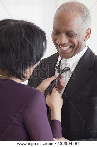 African woman adjusting husband's tie