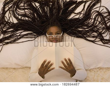 African woman on floor reading book