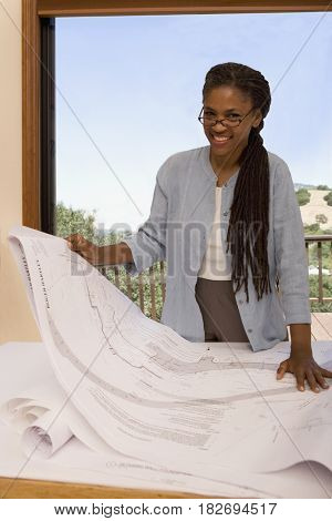 African woman looking at blueprints