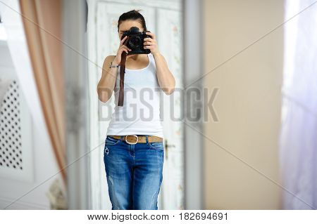 The girl the photographer at the time of shooting. The slender brunette holds the professional camera in hand. She is concentrated on work.