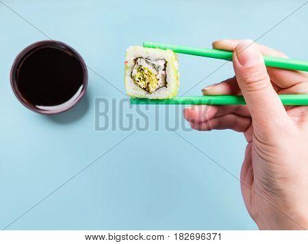 Girl holding roller with chopsticks on blue background