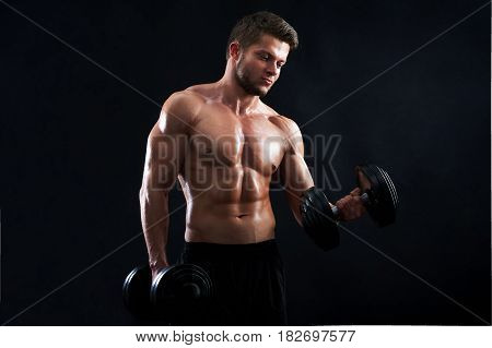 Horizontal studio shot of a young sexy male athlete exercising with heavy weights on black background posing shirtless showing off his hot toned ripped body confidence masculinity ambition motivation.