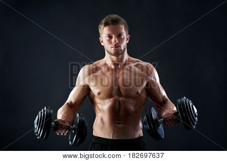 Studio shot of a young muscular fitness man working out shirtless showing off his perfect six-pack lifting heavy dumbbells on black background workout training exercising toning bodybuilding gym.
