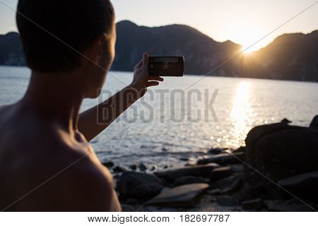 Young brunet taking pictures at seashore, facing sun