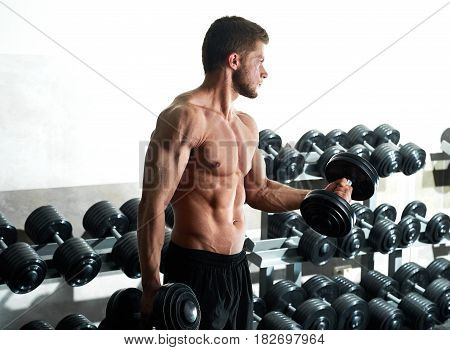 Shot of a handsome young sportsman with perfect muscular body working out shirtless at the gym pumping iron copyspace sports training people fitness lifestyle athletics concept.