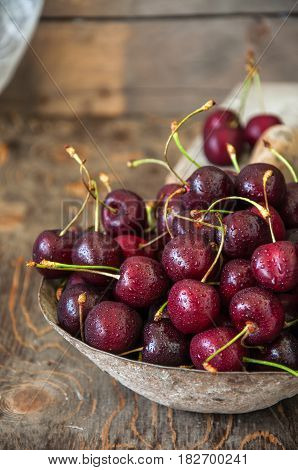 Sweet Fresh Ripe Burgundy Cherries With Water Drops In A Bowl On A Wooden Background. Close Up And C