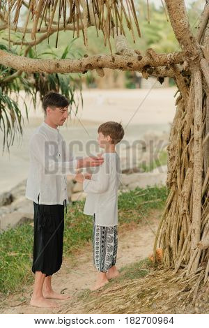 father and son standing under a tree in the Indian pants