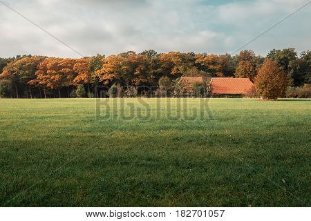Old Farmhouse In Meadow At Edge Of Autumn Forest.