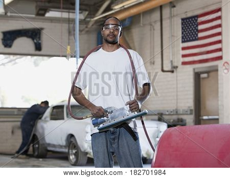 Mixed race worker holding equipment in auto body shop