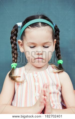 Little girl is praying. Mix asin kid