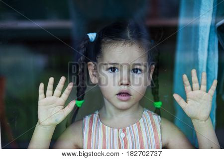 Portrat of sad mix asian girl by the window