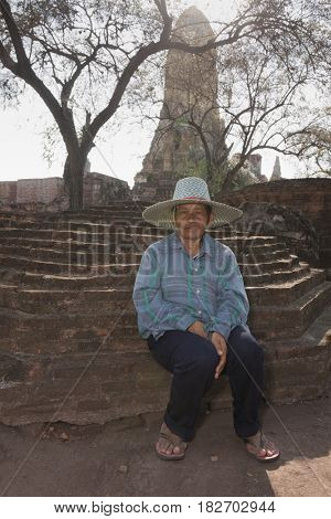 Asian man sitting outside temple