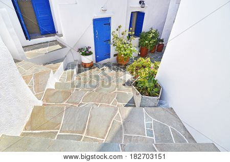 traditional cycladic yard with blue windows and flowers at Apollonia Sifnos Greece