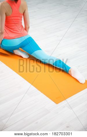 Photo of sportswoman doing exercises on orange rug in sports hall