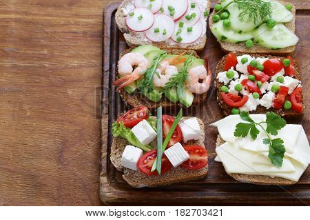 variety of sandwiches with different fillings (avocado, shrimp, fish, ham, vegetables)