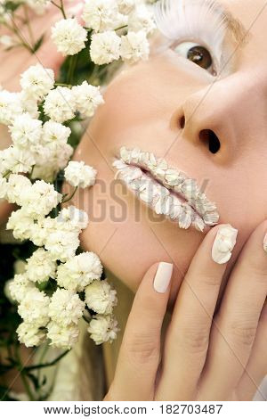 Summer white makeup and manicure with design on nails of baby's breath flowers closeup.
