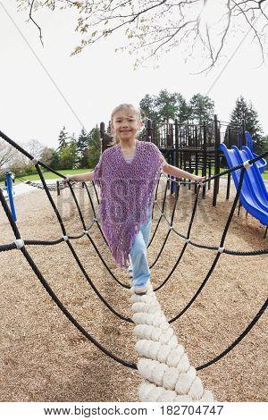 Mixed race girl on playground equipment