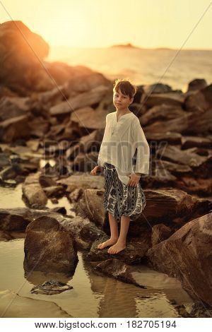 A hot day in the ocean a cute barefooted boy stands on large stones